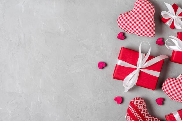 Fond de saint valentin avec coffrets cadeaux et coeurs sur fond de béton gris. concept minimal. pose à plat. vue de dessus avec espace copie