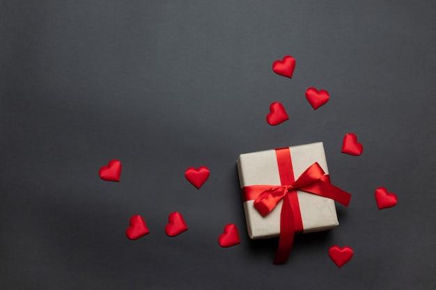 Fond de la saint-valentin. formes cadeau rouge boîte surprise cadeau sur fond sombre, concept de saint valentin. lay plat, vue de dessus, espace de copie