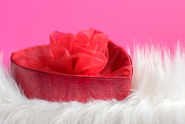 Fond saint valentin avec une fourrure blanche et une boîte de foyer rouge