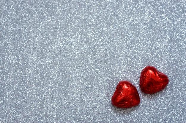 Fond saint valentin, maquette avec deux bonbons au chocolat en forme de cœur rouge