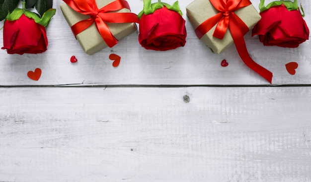 Fond de saint valentin avec rose rouge, coeurs et coffrets cadeaux sur table en bois blanc avec fond pour le texte.