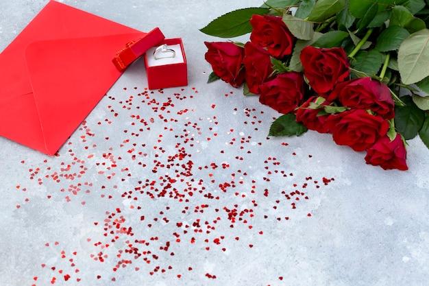 Fond de saint valentin avec roses rouges, bague en diamant et enveloppe rouge et coeurs rouges. vue de dessus