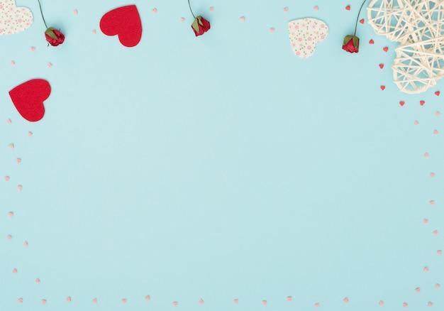 Fond de saint valentin avec rotin et coeurs en feutre, roses rouges et petits coeurs rouges et roses