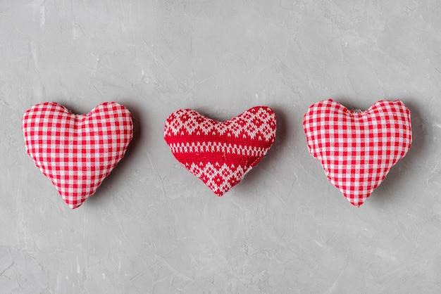 Fond de saint valentin avec textile et coeurs tricotés sur fond de béton gris. concept minimal. pose à plat. vue de dessus