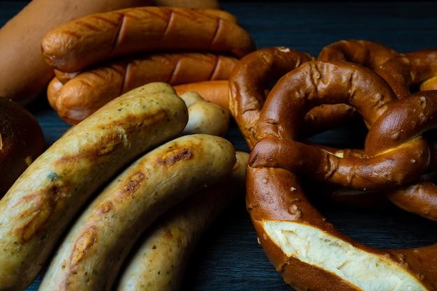 Fond de saucisses et de bretzels sur table en bois de style alimentaire sombre oktoberfest