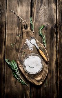 Fond de sel sel avec des branches de romarin sur la planche sur fond de bois