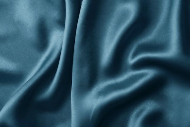 Fond de soie argenté avec plis. texture abstraite de la surface de soie ondulée