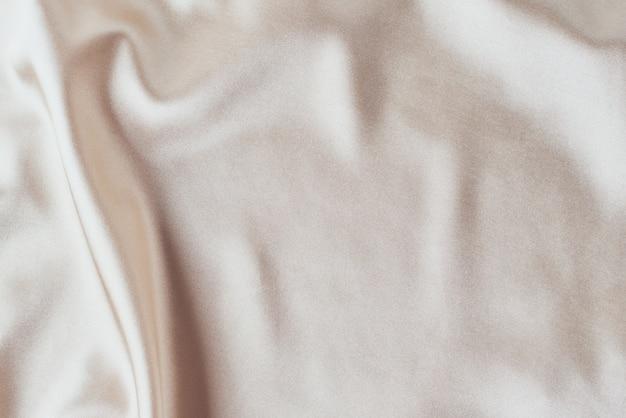 Fond de soie clair doré avec plis. texture abstraite de la surface satinée ondulée