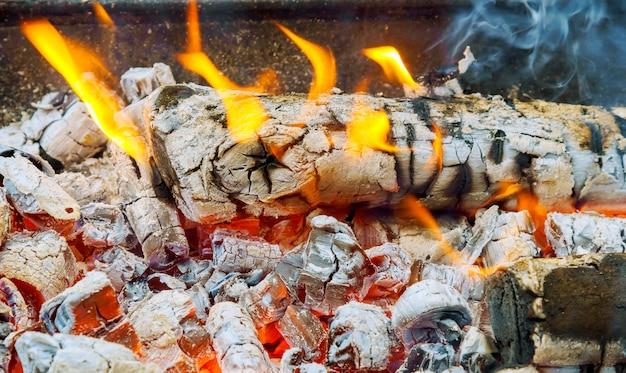 Fond sombre de bois carbonisé et de flammes lumineuses