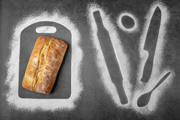 Fond sombre avec une miche de pain et de la farine contours de certaines choses pour la cuisson du couteau à pâtisserie