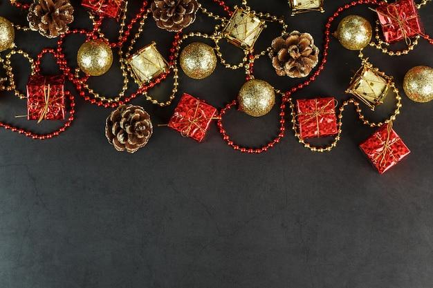 Fond sombre de noël ou du nouvel an avec des décorations rouges et or pour l'arbre de noël avec