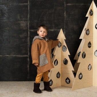 Sur un fond sombre petit garçon posant dans un manteau élégant près d'un arbre de noël en bois