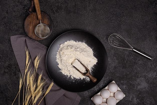 Fond sombre pour la cuisson avec des œufs, de la farine, du blé, un fouet