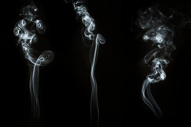 Fond sombre avec trois silhouettes fantastiques de fumée