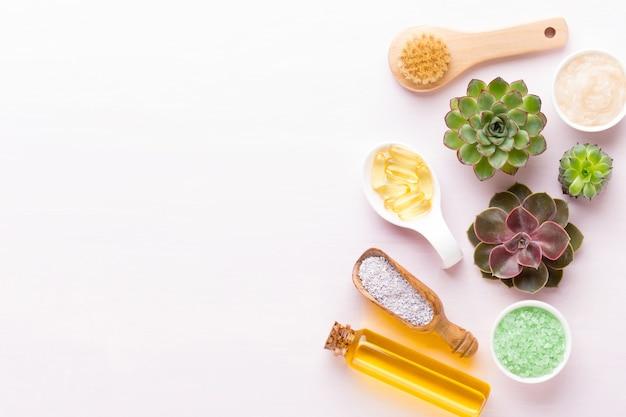 Fond de spa avec composition bio cosmétique et cactus à la main, pose à plat, espace pour un texte - image.
