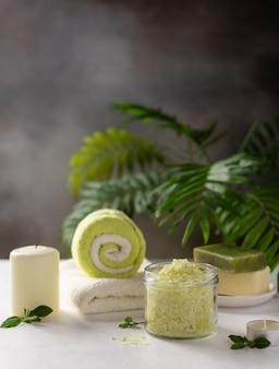 Fond de spa avec du sel de mer, du savon solide, des bougies et des serviettes de bain sur un fond de feuilles de palmier vert. concept de traitement et de détente spa beauté.