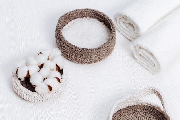 Fond de spa. fleur duveteuse de cotonnier et de sel de mer en boite sur un bois clair avec copie espace. articles pour spa.