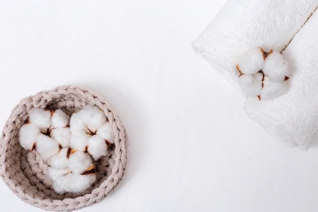 Fond de spa. fleur moelleuse de plante de coton en boîte et serviettes en coton blanc