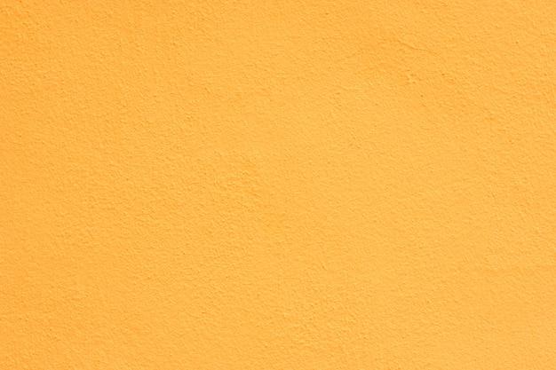 Fond de stuc jaune revêtu et peint à l'extérieur, fonte brute de ciment et texture de mur en béton