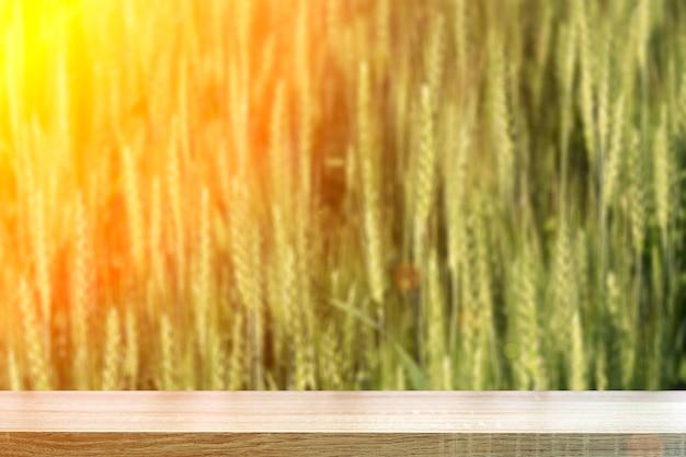 Fond de table de champ de blé. table en bois et récolte de blé sur un terrain ensoleillé d'été. agriculture, culture du seigle et culture bio eco food concept. photo de haute qualité