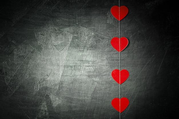 Fond de tableau noir vide avec guirlande de papier en forme de coeur