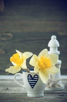 Fond avec une tasse à café bleue et des fleurs