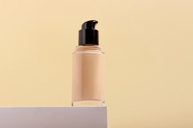 Fond de teint liquide en flacon sur support. correcteur facial sur fond beige avec espace de copie. maquette d'emballage avec espace de copie