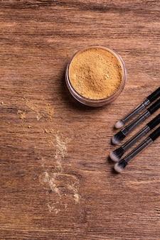 Fond de teint en poudre minérale avec pinceaux sur fond de bois. produits de beauté écologiques et biologiques