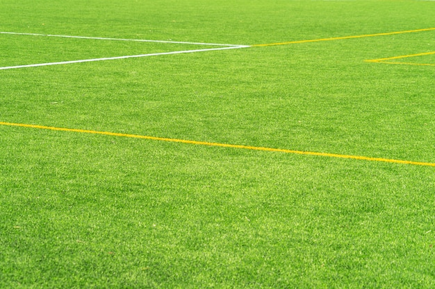 Fond de terrain de football de gazon vert gazon artificiel avec limite de ligne blanche et jaune. vue de dessus