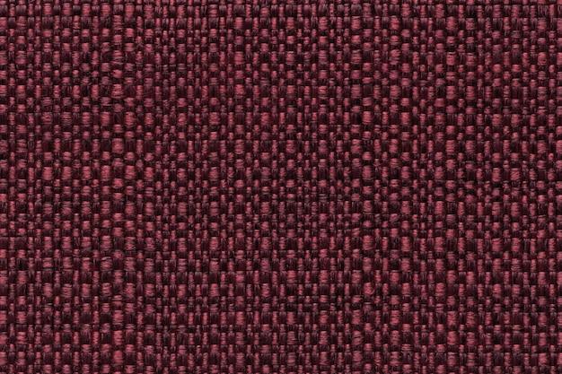 Fond textile rouge foncé avec motif à carreaux, gros plan. structure de la macro de tissu.