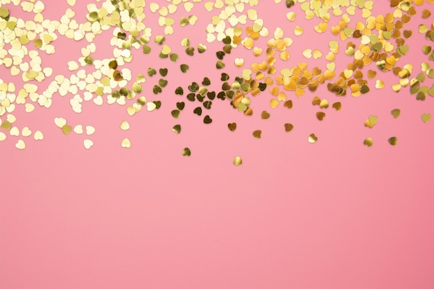 Fond texturé abstrait, paillettes en forme de coeur doré sur fond rose. saint valentin, amour, anniversaire, concept de fête.
