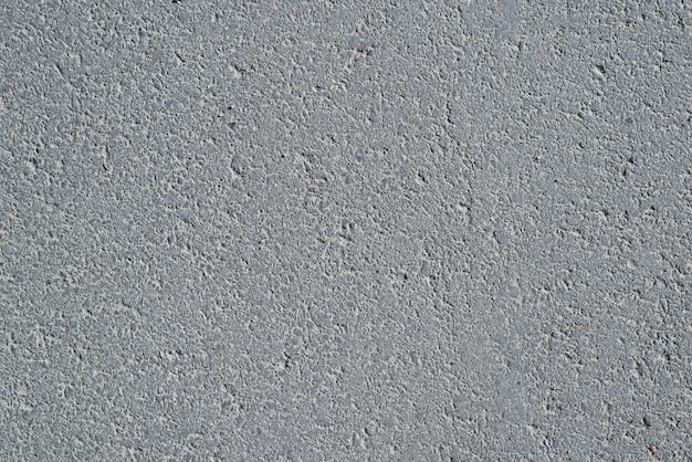 Fond texturé asphalte gris foncé, vue de dessus. toile de fond de surface de route rugueuse