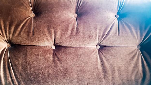 Fond de texture capitone marron, décoration en tissu touffeté doux en forme de losange de style rétro chesterfield avec boutons, décorer avec des boutons, gros plan.