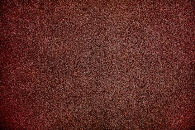 Fond texturé de gazon artificiel rouge