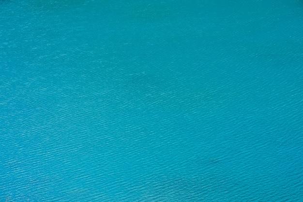 Fond texturé incroyable de la surface de l'eau azur propre calme.