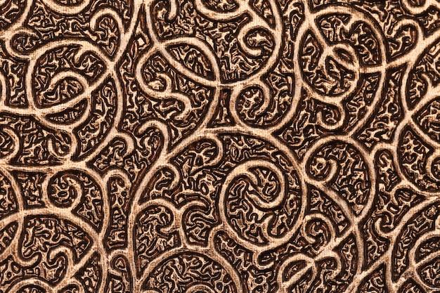 Fond texturé métallique plaqué or avec motifs.