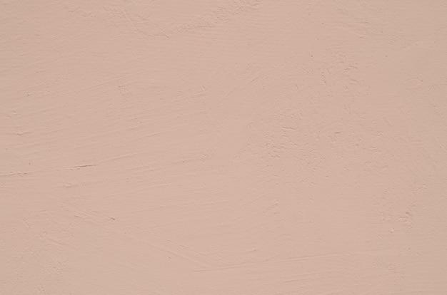 Fond texturé d'un mur de béton peint en rose clair