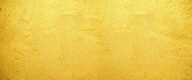 Fond de texture de mur doré pour la surface rugueuse du vieux mur de brique dorée.