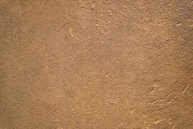 Fond de texture de mur de plâtre brun doré flou