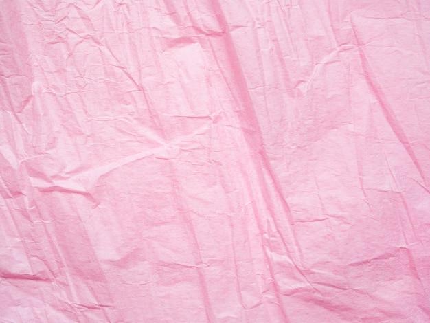 Fond de texture de papier froissé rose. plan macro sur du papier d'emballage. toile de fond froissée. effet texturé de la page. modèle abstrait, surface de fond rose. texture ridée de feuille