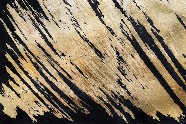 Fond ou texture de potal d'or. coups de pinceau abstraits brillants sur le noir.