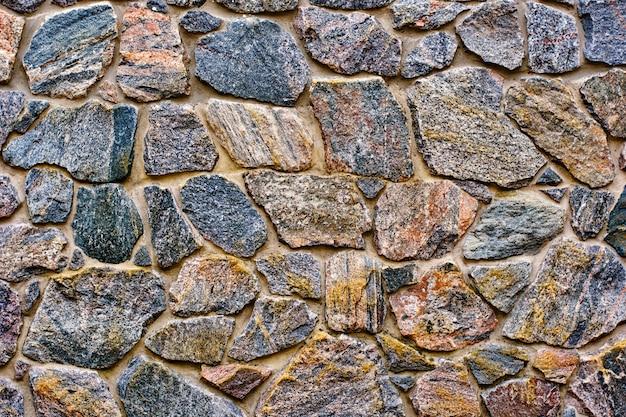 Fond d'une texture de revêtement de mur en pierre, briques de pierre brune
