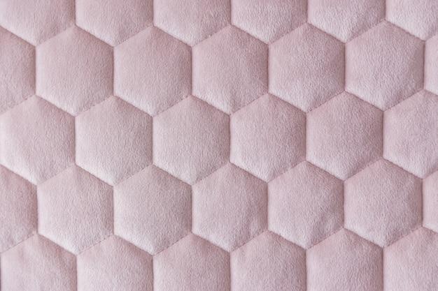 Fond texturé de tissu de maille hexagonale de couleur rose.