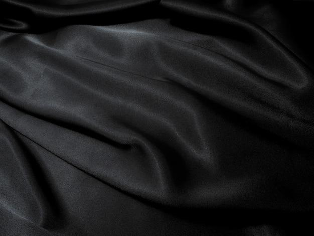 Fond de texture de tissu noir, couleur noire glissante de tissu ondulé, texte de satin de luxe