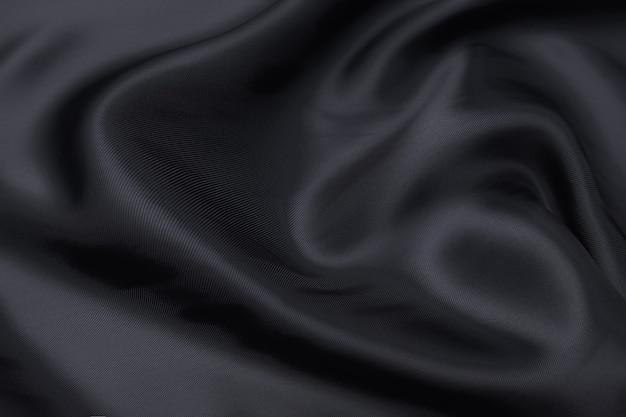 Fond de texture de tissu noir, couleur noire glissante de tissu ondulé, texture de tissu de satin ou de soie ou de laine de luxe.