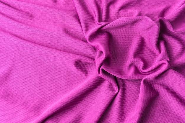Fond texturé en tissu rose. maillot de sport en tissu rose avec des vêtements texturés.