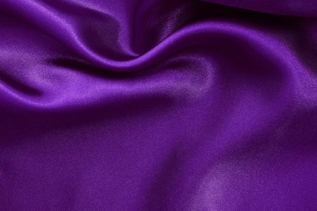 Fond de texture de tissu violet foncé, soie froissée ou lin.