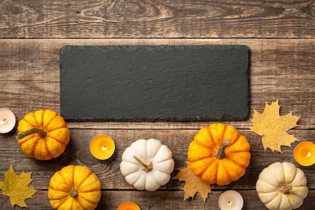 Fond de thanksgiving avec des citrouilles, des feuilles d'automne et des bougies