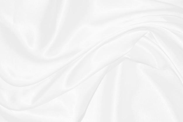 Fond de tissu texturé en soie blanchegros plan sur un tissu en satin ondulé avec des vagues douces
