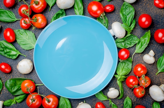 Fond avec des tomates, des champignons et des feuilles de basilic